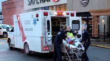 A man is loaded into an ambulance after a shooting involving the transit police in Surrey, B.C., on Sunday. (Shane MacKichan/THE CANADIAN PRESS)
