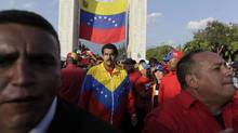 Venezuela's Vice-President, Nicolas Maduro, middle, walks alongside the coffin carrying the body of Hugo Chavez Wednesday as it is carried through the streets to a military academy where his body will lie in state in Caracas. (Rodrigo Abd/AP)