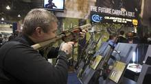 Mark Heitz, of Tactical Firearms in Kingston, N.H., looks over a civilian version of the Colt M4 carbine during the annual SHOT (Shooting, Hunting, Outdoor Trade) Show in Las Vegas January 15, 2013. Gun dealers at the show are reporting booming sales resulting from worries about possible gun control legislation. (STEVE MARCUS/REUTERS)