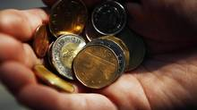 A man holds Canadian currency in this posed photograph in Toronto, October 22, 2008. (MARK BLINCH/REUTERS)