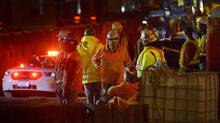 Workers look on at the Ottawa LRT construction site at Waller Street, where concrete from the roof of a tunnel fell, Thursday, Nov. 10, 2016 in Ottawa. (Justin Tang/THE CANADIAN PRESS)
