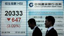 Pedestrians walk past an electronic board displaying the benchmark Hang Seng Index in Hong Kong on Jan. 7, 2016. Hong Kong stocks slumped again following a seven per cent collapse in mainland markets that caused trading to be suspended after just 30 minutes as China weakened its yuan-dollar value to a five-year low. (PHILIPPE LOPEZ/AFP/Getty Images)