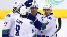 Vancouver Canucks' Jannik Hansen (36) celebrates his goal against the Arizona Coyotes with Ben Hutton (27), Chris Tanev (8) and Henrik Sedin (33) on Feb. 10, 2016. Back-to-back road victories over the Colorado Avalanche and Arizona Coyotes have Vancouver within shouting distance of the two wild-card spots in the Western Conference. (Ross D. Franklin/THE ASSOCIATED PRESS)