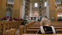 Worshippers pray at Marie Queen of the world cathedral, Thursday, June 23, 2016 in Montreal.