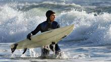 A surfer takes to the waves at Lawrencetown Beach, east of Halifax, on Dec.30, 2001. (ANDREW VAUGHAN/CP)