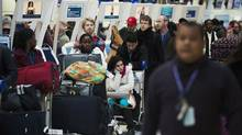 Frustrated passengers line up during flight delays and cancellations due to extreme cold weather and wind chill at Pearson International Airport in Toronto on Jan. 7, 2014. (AARON VINCENT ELKAIM/THE CANADIAN PRESS)