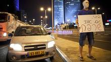 "An Israeli man covers his face with a bandage as others, not seen, block a highway in Tel Aviv on Sunday, July 15, 2012, during a protest against the economic policies of Israel's government and to show solidarity with Moshe Silman, an Israeli protester who set himself on fire on Saturday during a protest. The sign in Hebrew reads: ""Bibi you burned me too,"" referring to Israel's Prime Minister Benjamin Netanyahu by his nickname. (Oded Balilty/AP)"