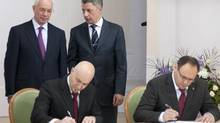 Ukrainian Prime Minister Mykola Azarov, top left, and Energy Minister Yuri Boiko, right, talk as Vladislav Kaskiv, right, the head of Ukraine's state investment agency, and a man the state investment agency identified as Jordi Sarda Bonvehi sign what the government thought was an agreement to build a liquefied natural gas terminal in Ukraine in Kiev Nov. 26, 2012. (STRINGER/REUTERS)