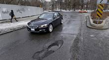 Drivers skirt around a pothole while turning onto Hoskin Ave. from Queens Park Crescent earlier this winter. (Fred Lum/The Globe and Mail)