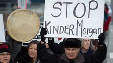 Grand Chief Stewart Phillip, president of the Union of B.C. Indian Chiefs, holds a sign while marching to a protest outside National Energy Board hearings on the proposed Trans Mountain pipeline expansion in Burnaby, B.C., on Jan. 19, 2016. (DARRYL DYCK/THE CANADIAN PRESS)