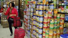 A Chinese visitor asks for the price of a canned infant formula at a store, in Hong Kong February 9, 2015. (REUTERS)