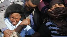 Relatives and family members of miners killed during clashes at Lonmin's Marikana platinum mine are comforted ahead of a memorial service in Rustenburg, 100 km (62 miles) northwest of Johannesburg, Aug. 23, 2012. (SIPHIWE SIBEKO/REUTERS)