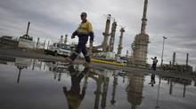 A worker is reflected in a puddle at Sydney's Caltex Oil refinery in Kurnell, Oct. 14, 2014, after the completion of shutting down the refinery and its transition to an oil storage facility. (Jason Reed/Reuters)