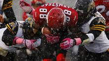 Calgary Stampeders Jason Armstead (C) is tackled by Hamilton Tiger Cats Ryan Hinds (L) and teammate Nathan Kanya during the first half of their CFL football game in Calgary, Alberta, October 20, 2012. (Todd Korol/REUTERS)