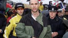 Police escort Paul Boyd from a rally supporting the U.S.-led war in Iraq in Vancouver, Sunday, March 30, 2003. The family of a man shot and killed by police say Boyd was a gentle soul who suffered from a mental disorder that could send him into a spiral of delusional paranoia. Police shot the 39-year-old last week after he attacked officers with a heavy chain and sent one to hospital with head injuries. (CHUCK STOODY/CP)