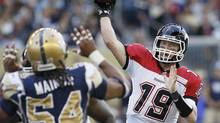 Calgary Stampeders' Bo Levi Mitchell (19) throws against Winnipeg Blue Bombers' Kenny Mainor (54) during the first half of their CFL game at Investors Group Field in Winnipeg Friday, July 26, 2013. (John Woods/THE CANADIAN PRESS)