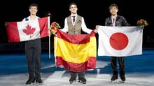 Men's gold medalist Javier Fernandez, of Spain, centre, silver medalist Patrick Chan, of Canada, left, and bronze medalist Nobunari Oda, of Japan, pose with their medals and their national flags during victory ceremonies at Skate Canada International in Windsor, Ont., on Saturday, October 27, 2012. (Paul Chiasson/THE CANADIAN PRESS)