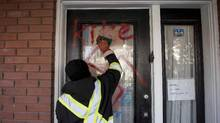 A graffiti removal worker cleans anti-Semitic graffiti, including a swastika, that was spray painted on the door of The Glebe Minyan and home of Rabbi Anna Maranta on Tuesday, Nov. 15, 2016 in Ottawa. (Justin Tang/THE CANADIAN PRESS)