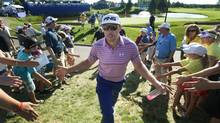 Hunter Mahan of the U.S. greets fans as he walks off the eighteenth green at the Canadian Open golf tournament at the Glen Abbey Golf Club in Oakville, July 26, 2013. (FRED THORNHILL/REUTERS)