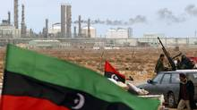 The Kingdom of Libya flag flies in front of a refinery in Ras Lanuf in this March 8, 2011, file photo. A new study says the recent uprising cost the country about 28 per cent of its gross domestic product. (GORAN TOMASEVIC/GORAN TOMASEVIC/REUTERS)