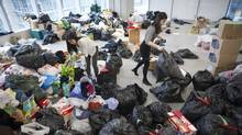 Rachel Lee, left, and Kelsey Devine, right, employees with Westbank, volunteer to organize about 11,000 Kilograms of items collected for Syrian refugees in Vancouver, British Columbia, Thursday, December 3, 2015. (Rafal Gerszak For The Globe and Mail)