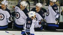Winnipeg Jets defenseman Dustin Byfuglien (33) is congratulated by teammates after scoring against the Boston Bruins in first period action during their NHL hockey game in Boston, Massachusetts November, 26 2011. (ADAM HUNGER/REUTERS/ADAM HUNGER/REUTERS)