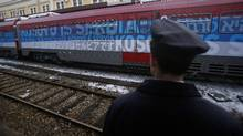 """A railroad worker stands by the first train decorated with letters that read """"Kosovo is Serbian"""" written in twenty languages departing from the Belgrade to Mitrovica, Kosovo at Belgrade's railway station, Serbia, Saturday, Jan. 14, 2017. Serbia has launched a railway link to Serb-dominated northern Kosovo despite protests from authorities in Pristina who described the move as a provocation and an aggressive violation of Kosovo's sovereignty. (Darko Vojinovic/The Associated Press)"""