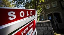 """A """"For Sale"""" sign stands in front of a home that has been sold in Toronto, Canada, June 29, 2015. REUTERS/Mark Blinch (© Mark Blinch / Reuters)"""