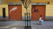 A girl stands next to a closed down business in Madrid July 27, 2012. (SUSANA VERA/REUTERS)