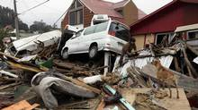A woman climbs over the debris of her destroyed house in Dichato, Chile, Monday, March 1, 2010. (NATACHA PISARENKO/ASSOCIATED PRESS)