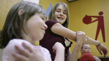 Cassidy Robinson, right, and her little buddy Lauren Hardt stretch after completing the Healthy Buddies fitness loop in the gym of their school in Sechelt, B.C. (Lyle Stafford/The Globe and Mail)