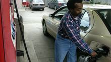 Cab drive Omar Mohamed fills his car with gas at an Esso gas station on King Street West in Toronto. (The Globe and Mail)
