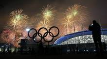 A man takes a photograph of fireworks during the closing ceremony of the 2014 Winter Olympics in Sochi, Russia, on Feb. 23, 2014. (PETR DAVID JOSEK/ASSOCIATED PRESS)
