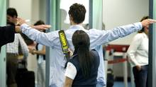 A member of The Canadian Air Transport Security Authority uses a hand-held metal detector on a passenger at the Vancouver International Airport June 20, 2008. (John Lehmann/Globe and Mail/John Lehmann/Globe and Mail)