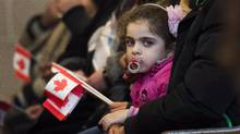 Newly-arrived Syrian refugees take part in a mass at the Armenian Community Centre in Toronto on December 16, 2015. (Nathan Denette/THE CANADIAN PRESS)