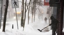 A man clears a sidewalk in blizzard conditions in Halifax on Friday, Jan. 3, 2014. (ANDREW VAUGHAN/THE CANADIAN PRESS)