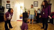 Neema and Jay Mertelly, their mother Nila and public health nurse, Maple Cardona get active with the hokey-pokey after dinner. (Deborah Baic/The Globe and Mail)
