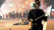 A man comforts his girlfriend after police knocked her down during the Stanley Cup riots in Vancouver on June 15. (Rich Lam/Getty Images)