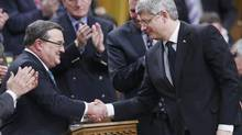 Finance Minister Jim Flaherty shakes hands with Prime Minister Stephen Harper after he delivered the federal budget in the House of Commons on Parliament Hill on March 21, 2013. (CHRIS WATTIE/REUTERS)