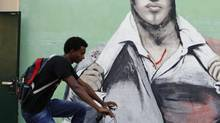 An African migrant rides his bicycle past a mural in Tel Aviv June 4, 2012. (BAZ RATNER/REUTERS)