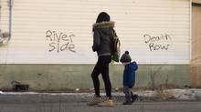 A woman and a young boy walk through the streets in the northern Ontario First Nations reserve in Attawapiskat, Ont., on Monday, April 16, 2016. (Nathan Denette/THE CANADIAN PRESS)