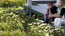 Police and forensic team members take a break in the shade of a home inside the red zone in Lac-Mégantic, PQ on July 14, 2013. (Peter Power/The Globe and Mail)