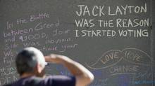 A man reads from a wall that has been made into a tribute to the late NDP leader Jack Layton at Nathan Phillips Square in Toronto on Tuesday August 23, 2011. (Aaron Vincent Elkaim/Aaron Vincent Elkaim/THE CANADIAN PRESS)