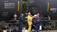 People from several juristictions including the Ministry of the Environment for Canada and Quebec, and the RCMP prepare to do some investigative work in the area of the nine remaining tank cars sitting on the tracks in Nantes, PQ on July 11, 2013. (Peter Power/The Globe and Mail)