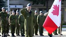 "Lieutenant-Colonel Darcy ""Plug"" Molstad, Canadian Air Task Force commander and F-18 pilot, salutes during the National Day of Honour ceremony on the parade grounds in Câmpia Turzii, Romania during NATO reassurance measures on May 9, 2014. (MCpl Patrick Blanchard, Canadian Forces Combat Camera)"