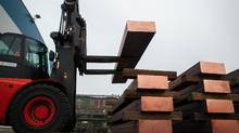 A forklift truck lowers a copper slab onto wooden blocks for storage in Hamburg, Germany, in this file photo. (Krisztian Bocsi/Bloomberg)