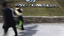 Pedestrians walk past a sign for the head office of SNC Lavalin in downtown Montreal March 26, 2012. (CHRISTINNE MUSCHI/REUTERS)