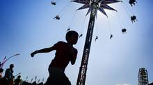 A boy runs by the Swing Tower. The CNE's midway has more than 50 rides and 125 games. (Aaron Vincent Elkaim/The Canadian Press/Aaron Vincent Elkaim/The Canadian Press)