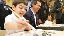 Ontario Premier Dalton McGuinty makes crafts with pupils at St. Fidelis Catholic Elementary School in Toronto after announcing renewed funding for elementary schools across the province to support a locked-door policy while students are in class. (Chris Young/THE CANADIAN PRESS)