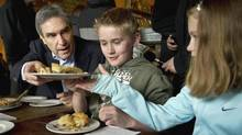 Liberal Leader Michael Ignatieff hands over a piece of pie to Lily Murphy, 9, as her brother Brien, 11, looks on at the Savary Island Pie Company Monday, April 25, 2011 in Vancouver. (Paul Chiasson/The Canadian Press)